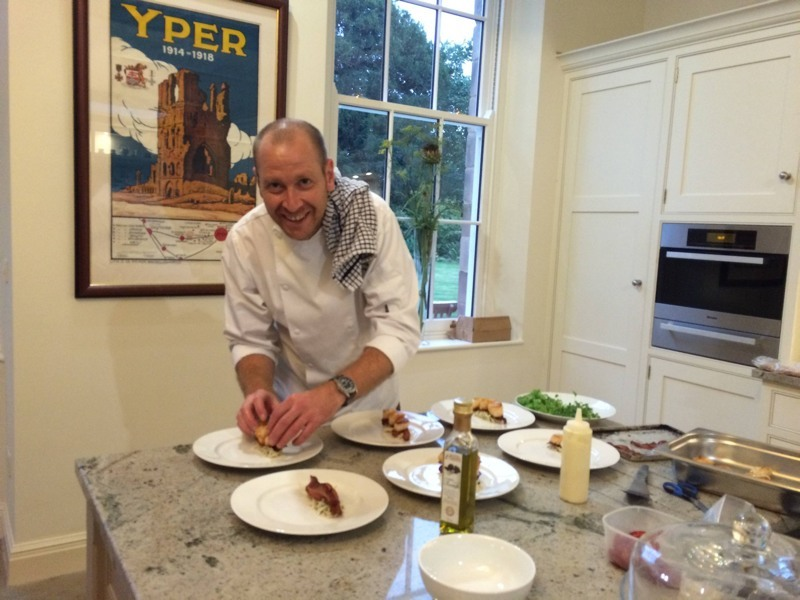 Charlie Ratcliffe in his white chef's apron , tea towel over shoulder, plating up food on the granite island unit at Darley house for our fully catered art retreats