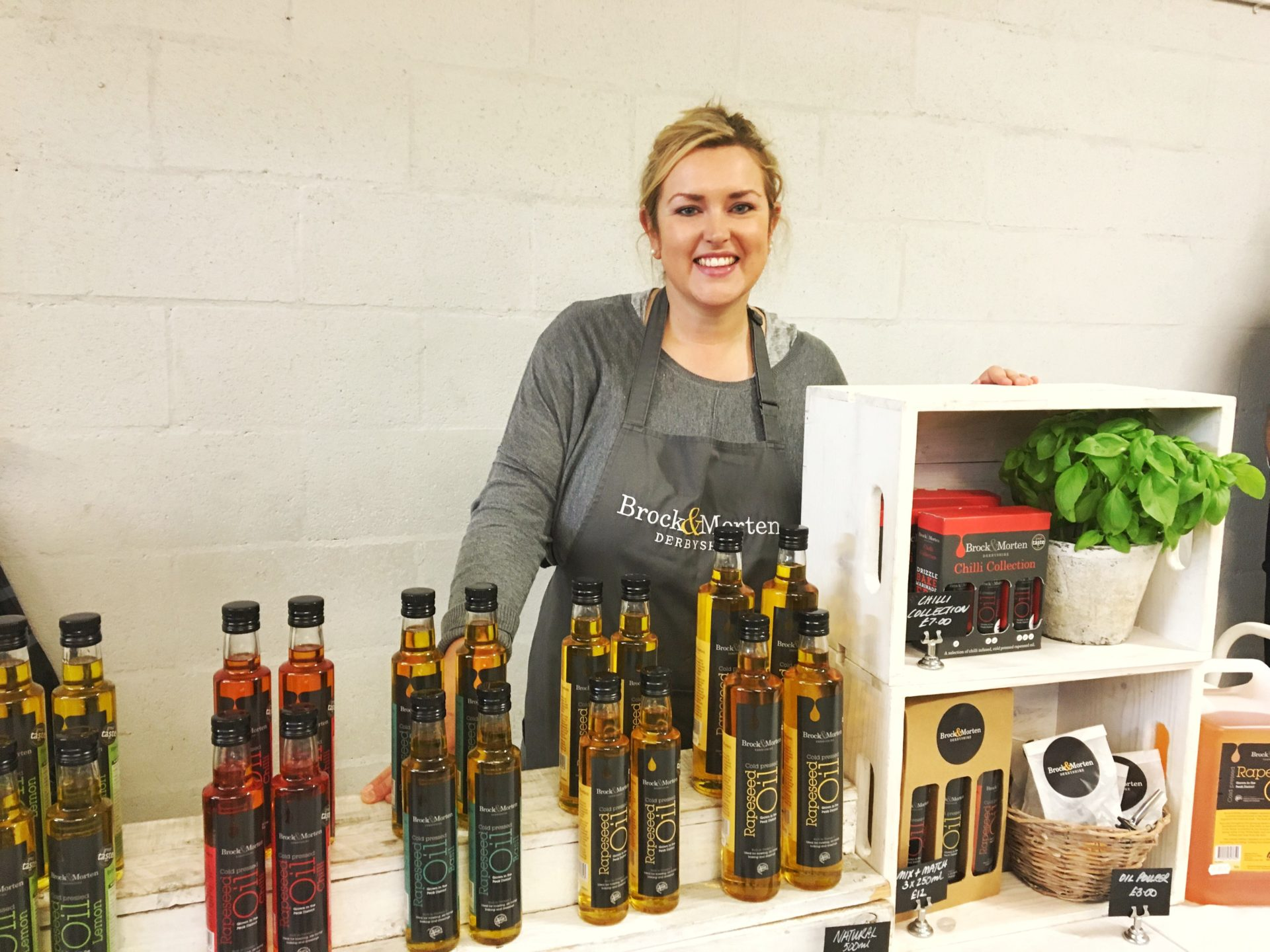 A smiling Kate, co-owner of Brock & Morten, at the Bakewell Farmer's Market August 2016 with her stall of colourful rapeseed oils