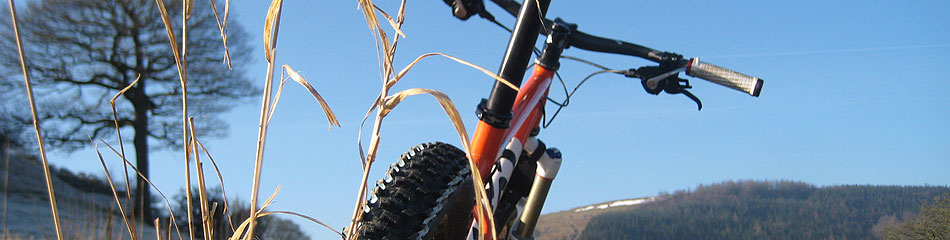 A close up of a section of a mountain bike, with its thick tyres, with blue skies and the tops of rolling Derbyshire hills in the background