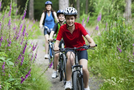 A photo Carsington Water website showing children wearing helmets cycling on the paths around Carsington Water