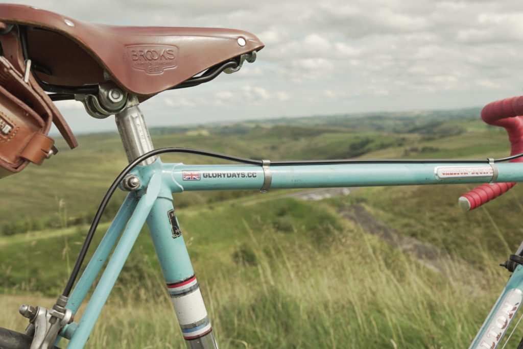 Close up of a Glory Days Bike vintage bike (leather saddle and duck egg blue cross bars) with the Peak District scenery in the background