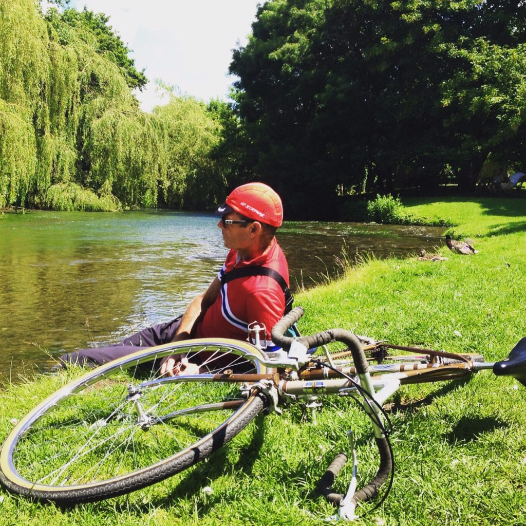 A cyclist resting, sitting beside his bike, on the grassy banks of a river, with the river and a weeping willow in view, courtesy of Glory Days Bikes