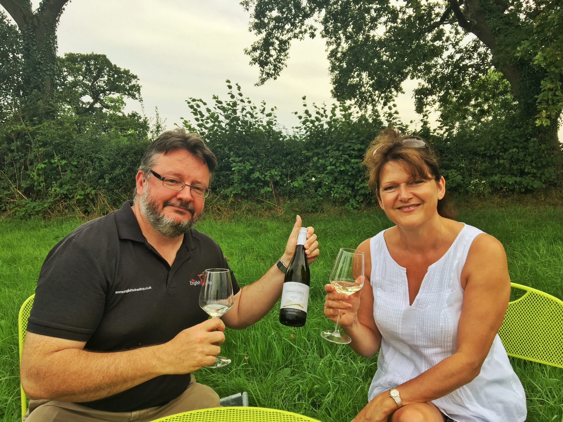 Lucy Arterton and Barry Lewis (of Amber Valley wine) sampling the Lindway White in a field with hedgerows and trees in the background