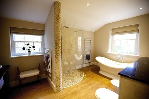 A large, light bathroom with standalone roll-top bath, curved glass shower screen, mosaic tiling and wooden floors.