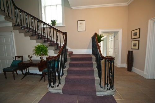 A wide stone staircase with wooden balustrade and lilac-coloured carpet runner leads upstairs.