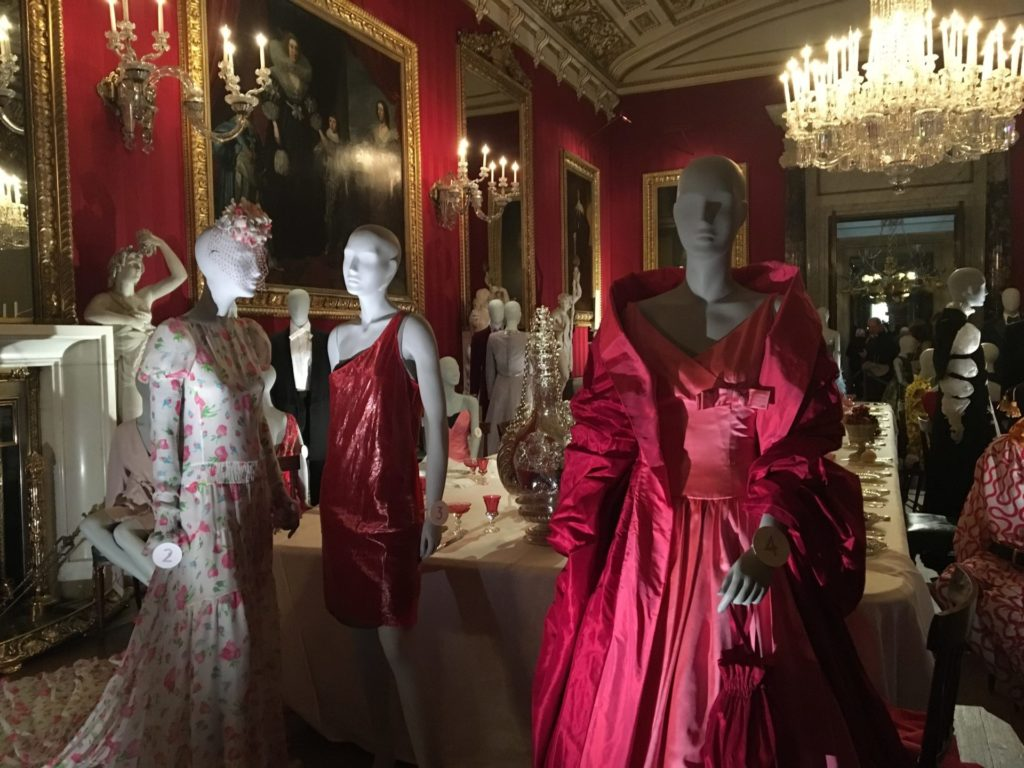 Mannequins on display in the crimson Chatsworth dining room, dressed in various shades of pinks and reds evening dresses to match