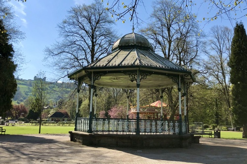A pretty and decorative, Victorian bandstand on lush green grass with clear blue skies.