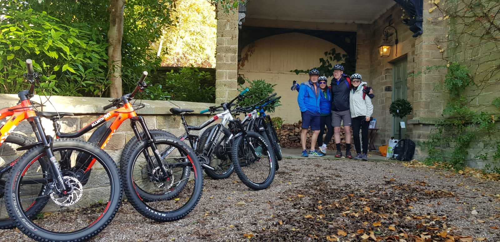 E-mountain bikes in the foreground of Darley House Entrance.  Four riders standing by the door